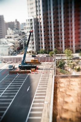 soku_12417.jpg :: 建築現場 風景 街並み 都市の風景 重機 移動式クレーン レッカー ミニチュア風 フィルム 銀塩